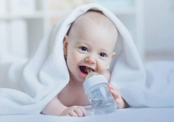 Baby liegt unter einer Decke und trinkt aus einer Babyflasche.