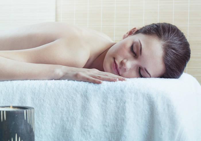 Frau entspannt auf einer Massagebank.