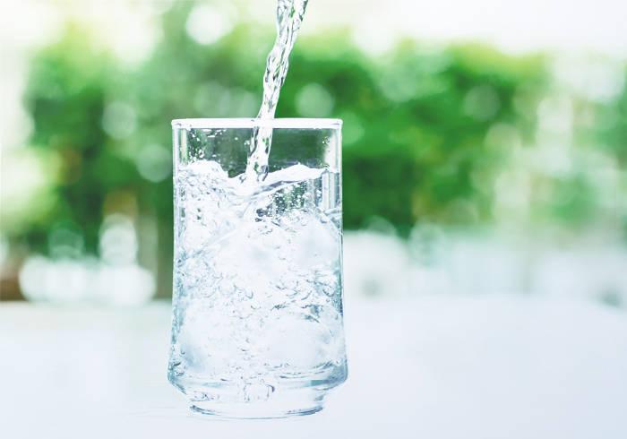 Wasser wird in ein Glas eingegossen.