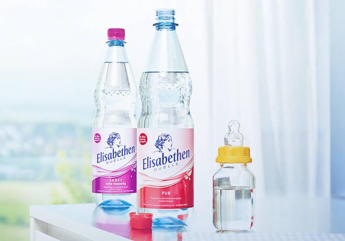 Elisabethen Quelle Pur und Sanft neben einer Babyflasche.