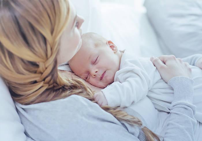 Frau hält schlafendes Baby in ihren Armen.