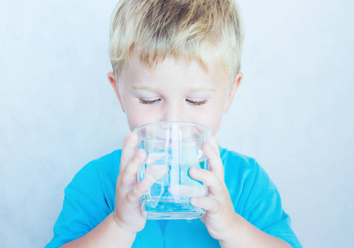Kind trinkt Wasser aus einem Glas.