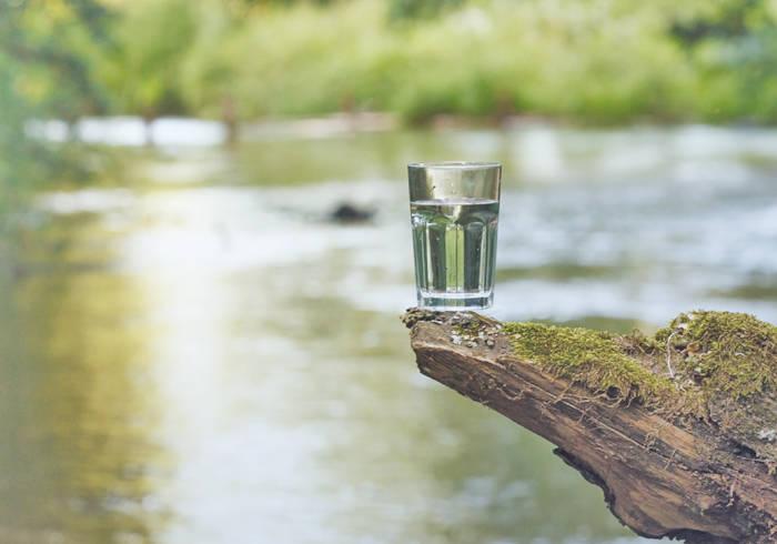 Glas steht auf einem Felsen, im Hintergrund ist ein Fluss.