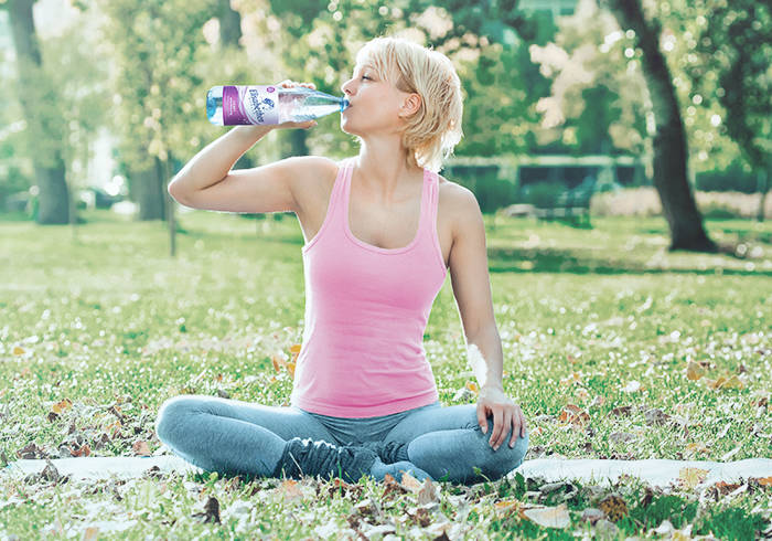 Eine Frau in Sportklamotten sitzt draußen auf einer Wiese und trinkt Elisabethen Quelle Sanft aus der Flasche.
